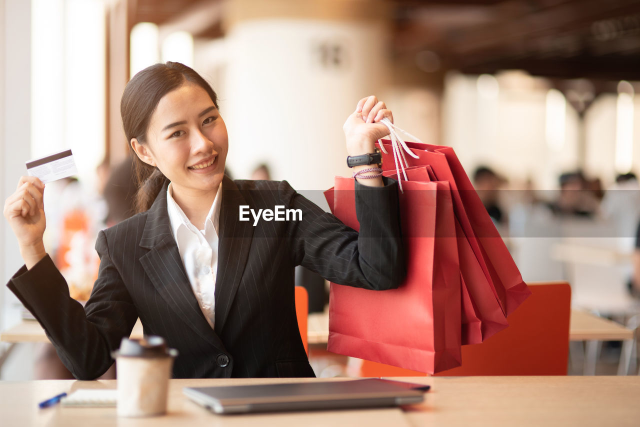 Portrait of young businesswoman holding credit card and shopping bags restaurant