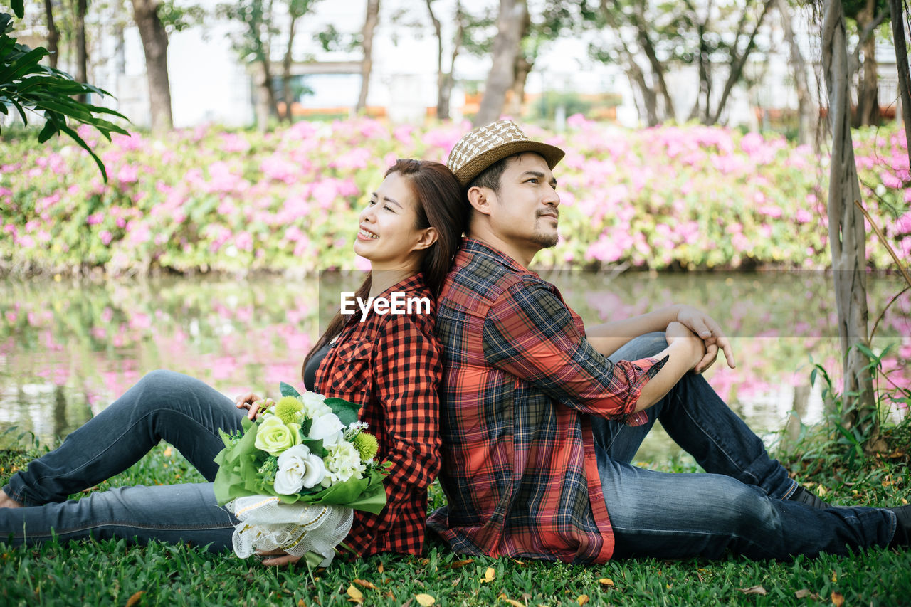plant, young adult, two people, couple - relationship, sitting, young men, togetherness, heterosexual couple, adult, love, young couple, emotion, young women, full length, casual clothing, grass, flower, hat, nature, leisure activity, positive emotion, girlfriend, boyfriend, outdoors