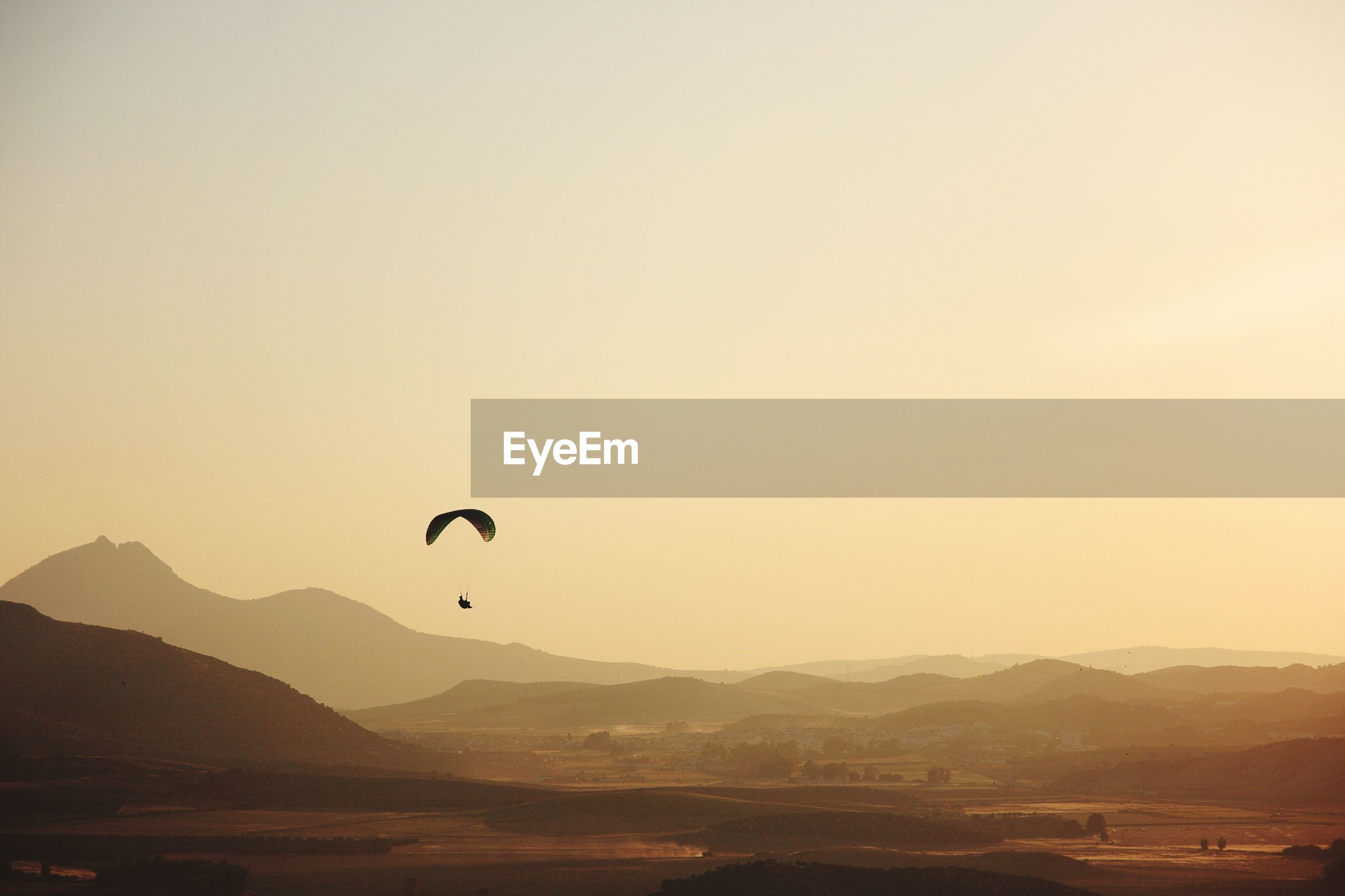 Parachute over mountains against clear sky