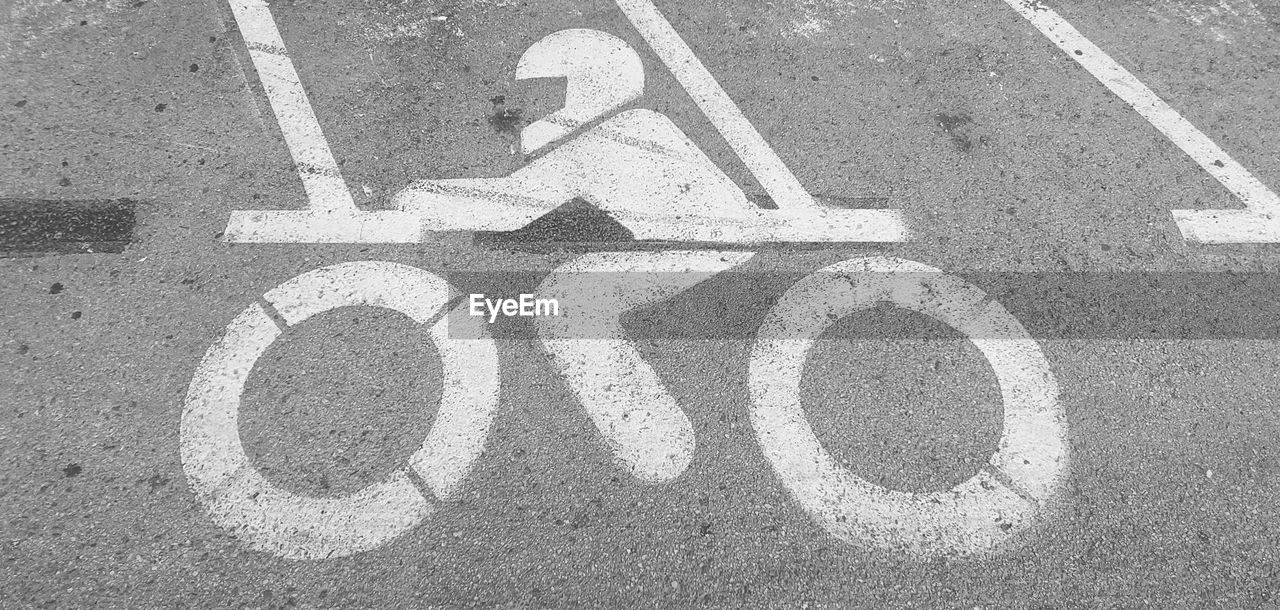 road, communication, sign, high angle view, marking, transportation, symbol, road marking, city, no people, day, street, asphalt, bicycle lane, road sign, guidance, outdoors, text, sunlight, information, message