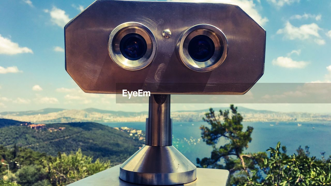 binoculars, coin operated, close-up, nature, cloud - sky, sky, coin-operated binoculars, day, focus on foreground, plant, outdoors, no people, landscape, security, surveillance, metal, beauty in nature, tree, environment, optical instrument, hand-held telescope