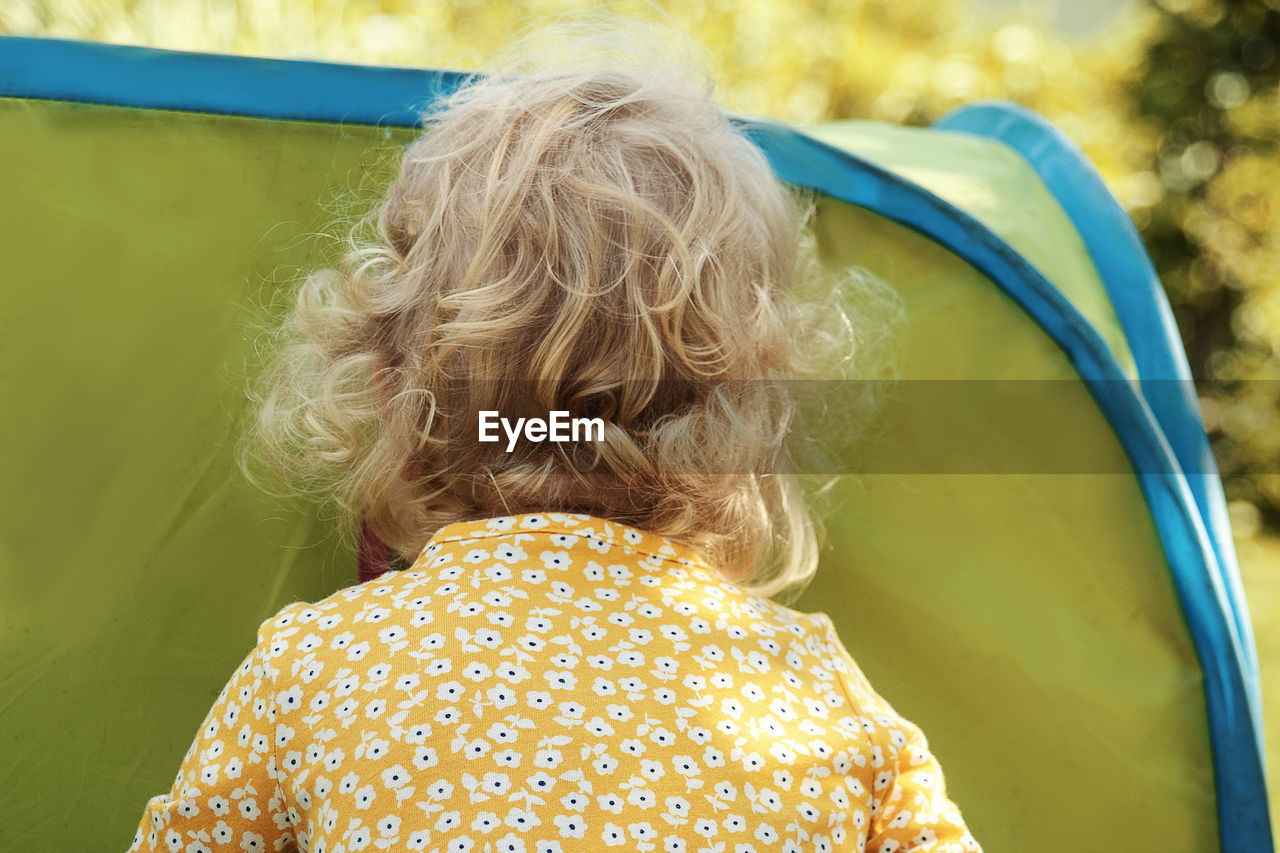 Little girl with blonde curly hair peeking into tent.