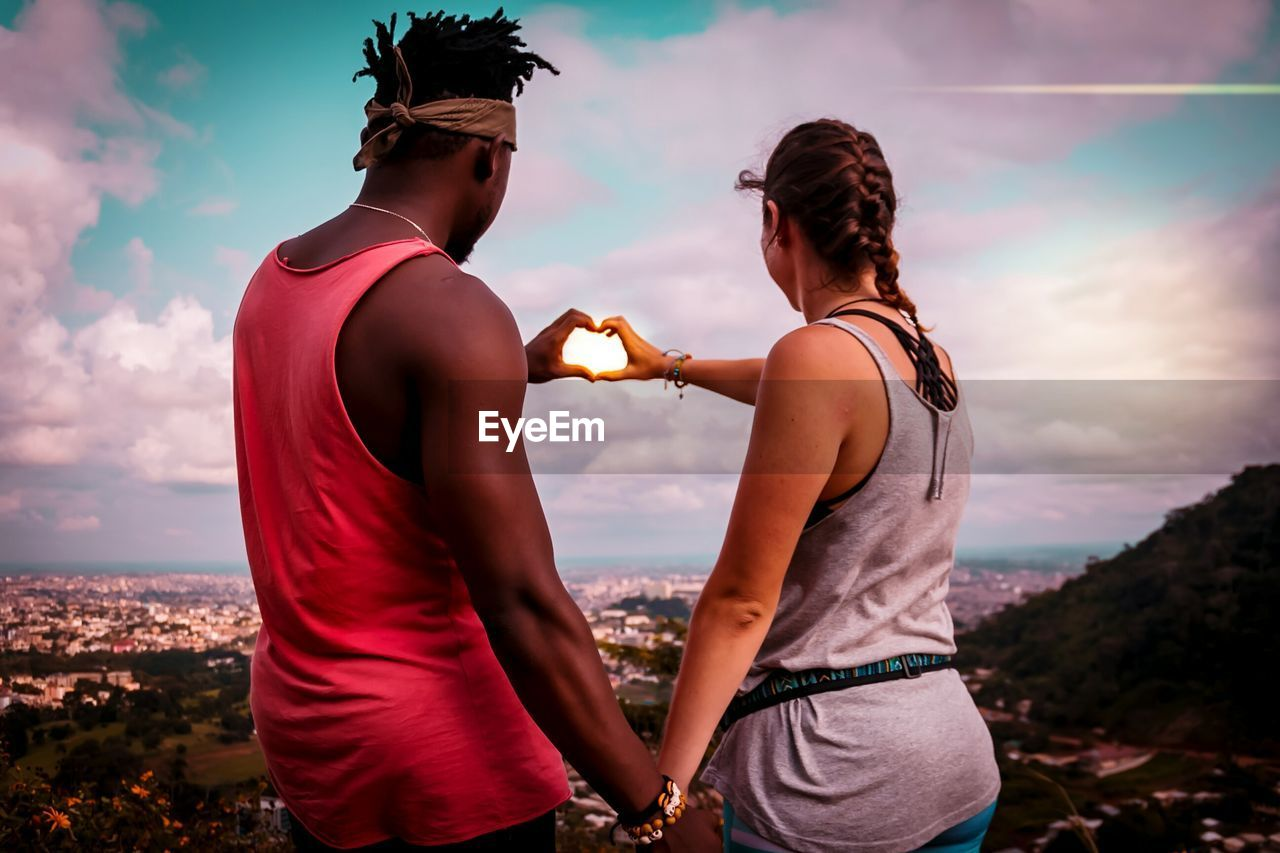 Rear View Of Man And Woman Making Heart Shape With Hands While Standing On Mountain Against Sky