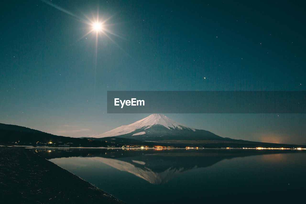 Mount fuji reflecting in lake against sky at night