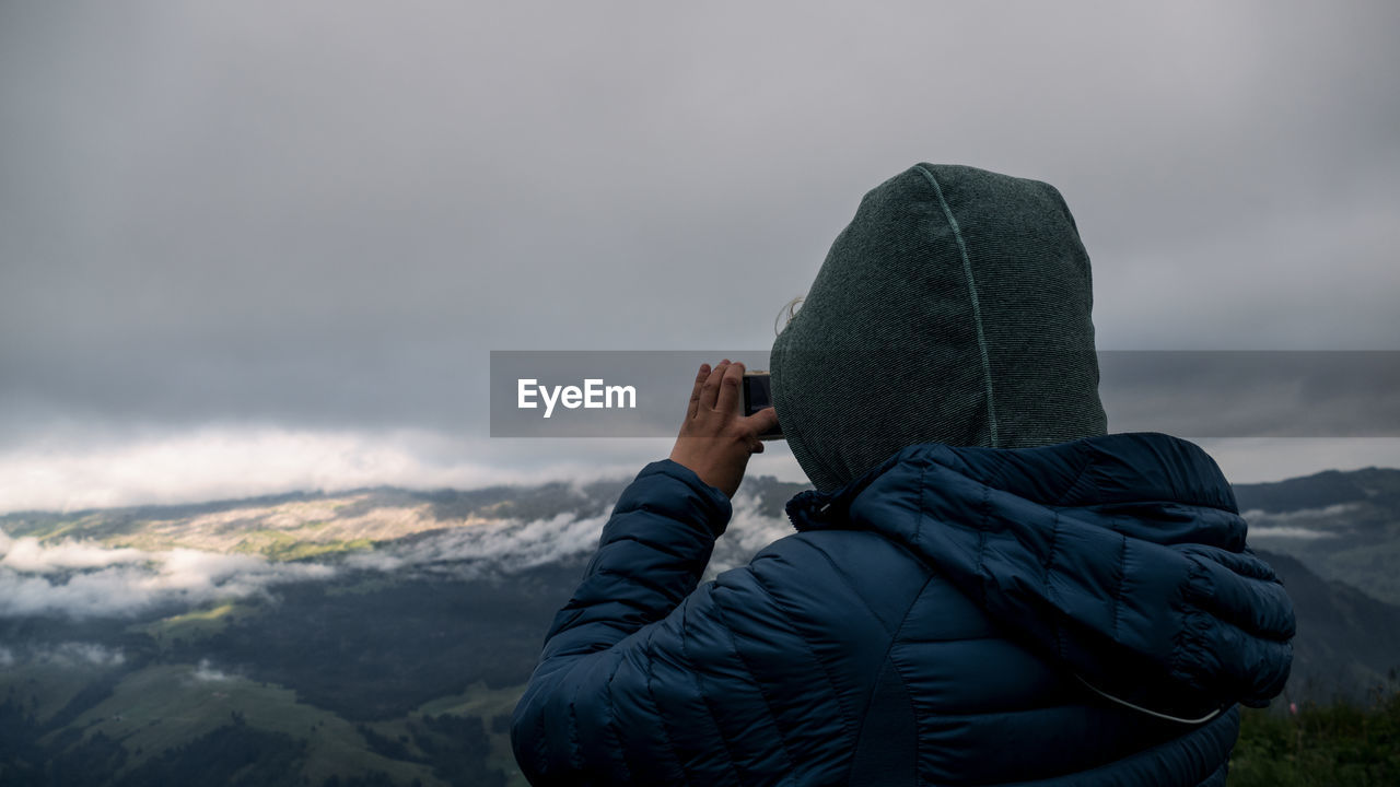 Rear view of woman photographing while standing on mountain against cloudy sky