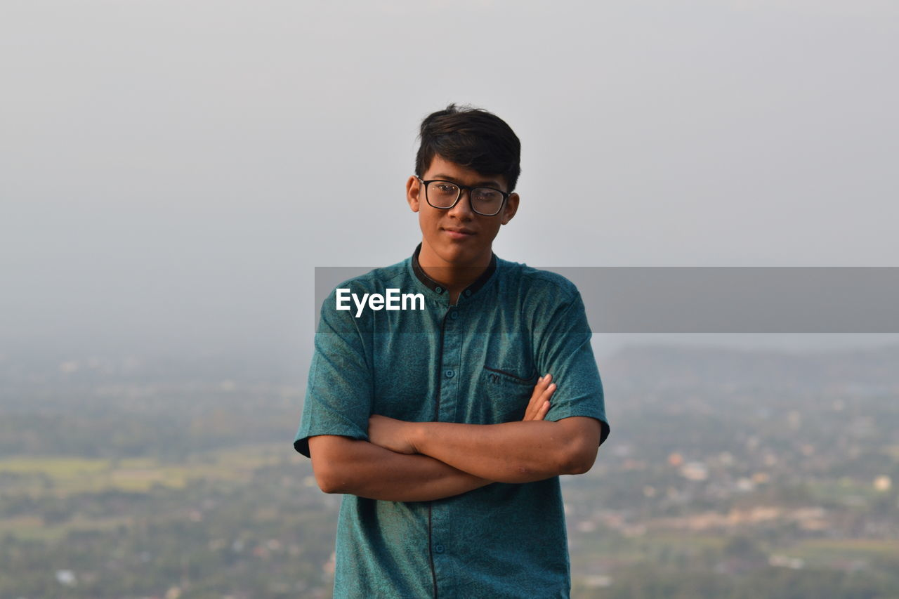 Portrait of young man standing against landscape