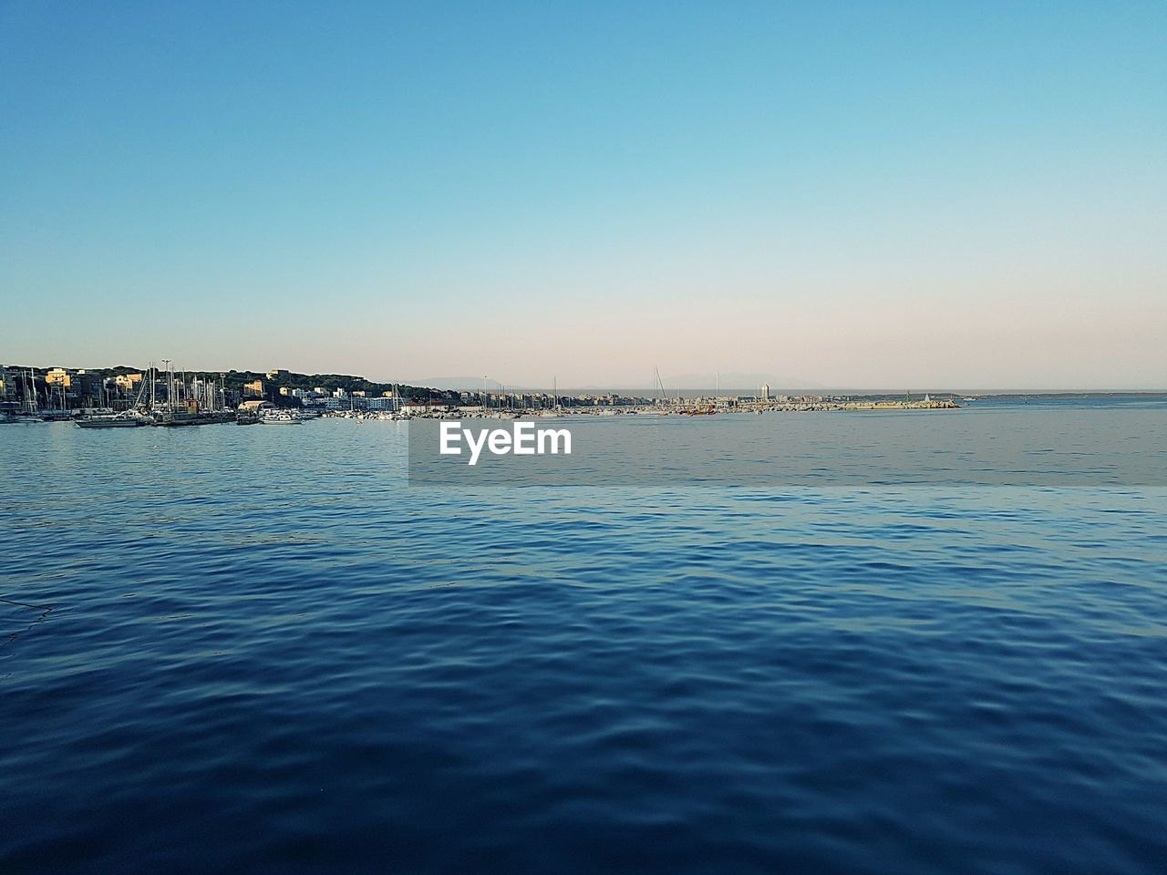 SCENIC VIEW OF SEA AND CITYSCAPE AGAINST CLEAR BLUE SKY