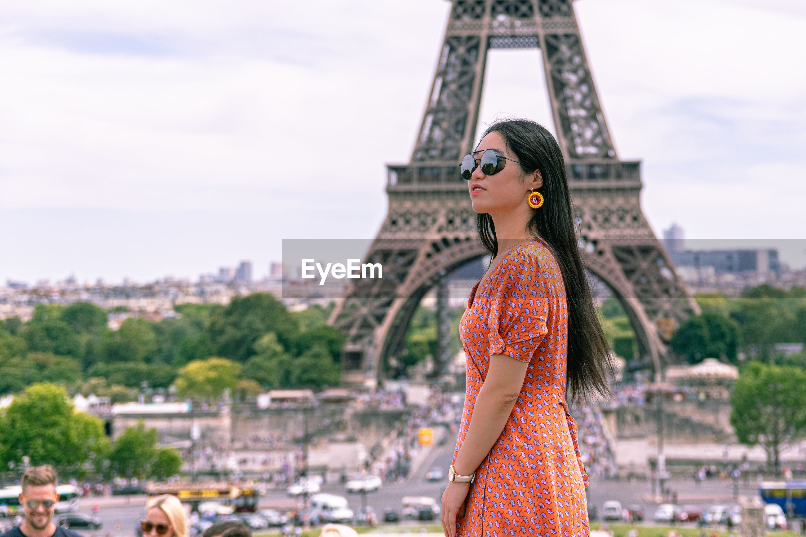 Side view of woman standing against eiffel tower