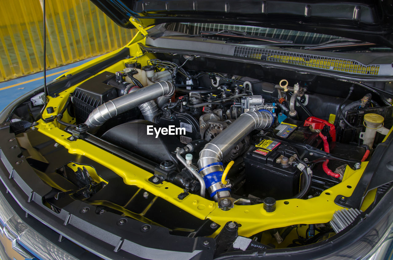 technology, machinery, industry, engine, motor vehicle, car, no people, mode of transportation, close-up, transportation, equipment, metal, vehicle part, indoors, complexity, automobile industry, land vehicle, high angle view, factory, yellow, production line
