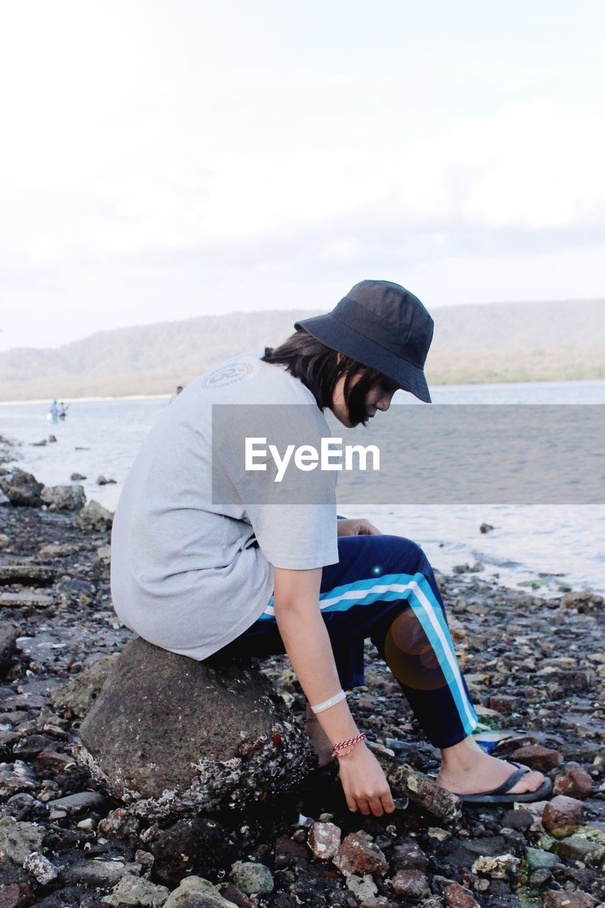 water, one person, real people, sea, side view, lifestyles, casual clothing, leisure activity, day, nature, full length, beach, solid, rock, land, rock - object, sitting, beauty in nature, outdoors, pebble
