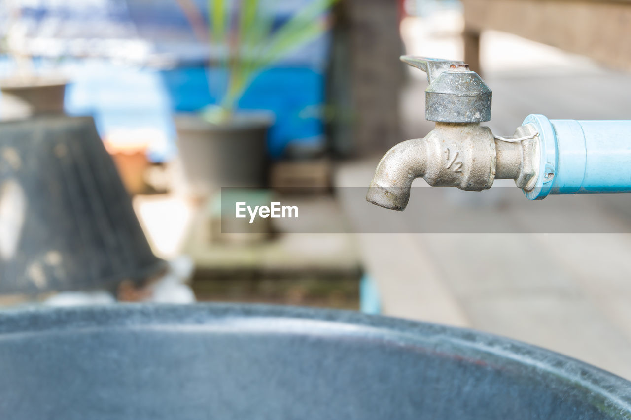 focus on foreground, metal, close-up, day, no people, outdoors, selective focus, valve, creativity, water, pipe - tube, faucet, blue, hose, art and craft, nut - fastener, design, industry, silver colored