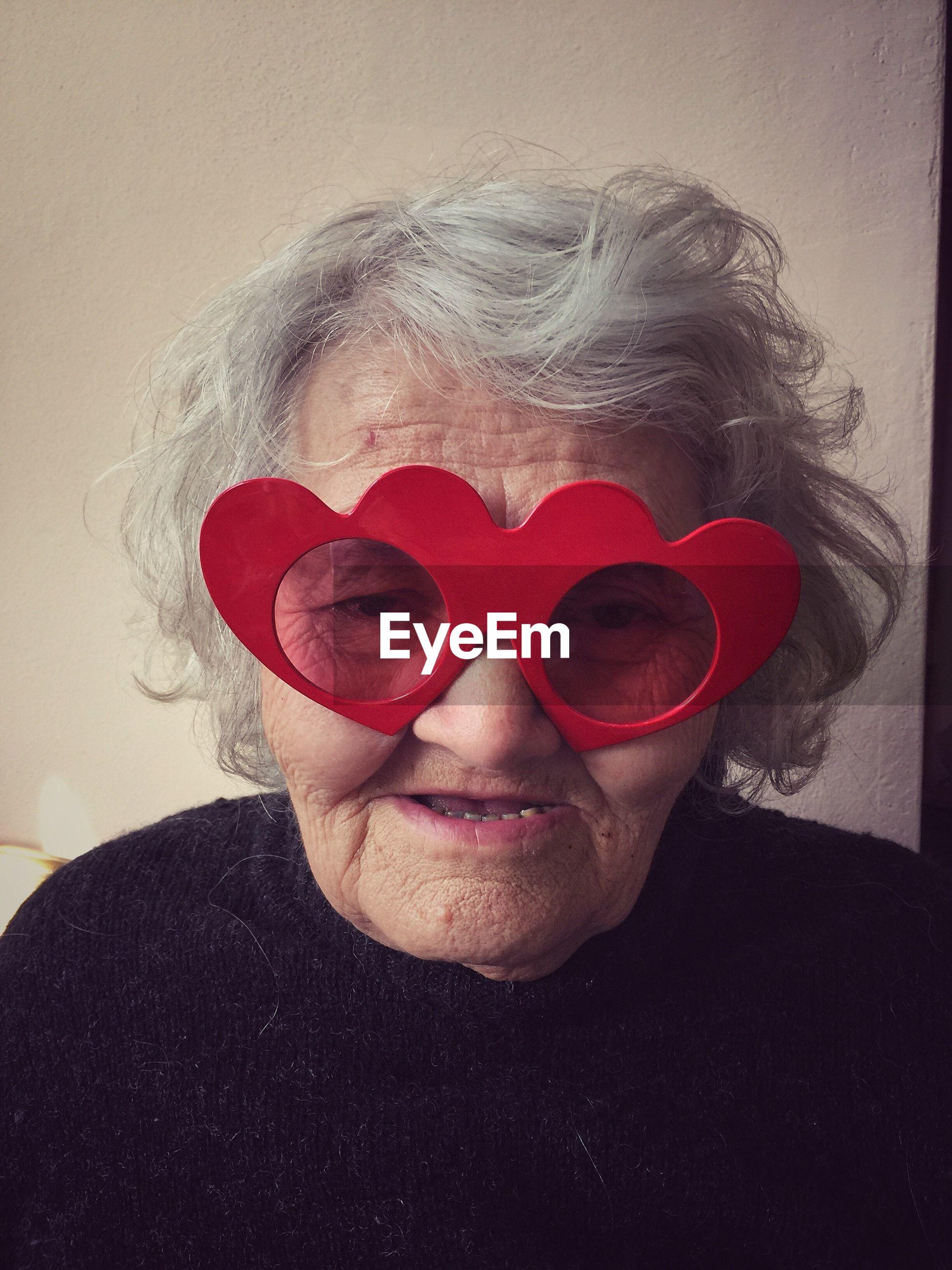 Portrait of senior woman wearing heard shape novelty glasses against wall