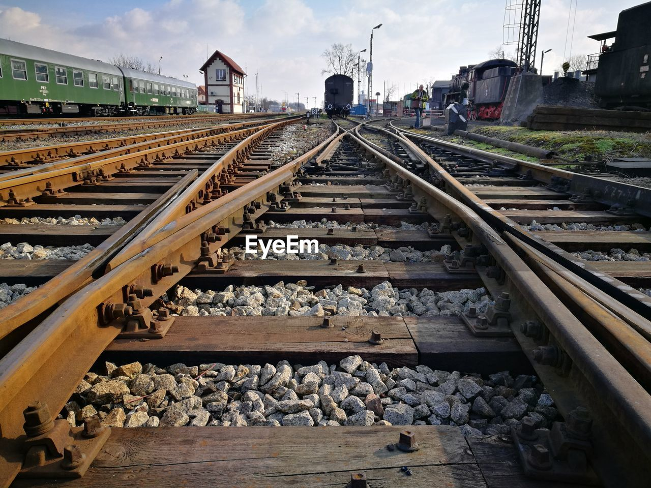 track, rail transportation, railroad track, transportation, direction, solid, the way forward, gravel, railroad tie, rock, sky, metal, rock - object, stone - object, day, nature, diminishing perspective, cloud - sky, mode of transportation, built structure, no people, outdoors, surface level, pebble, shunting yard, long