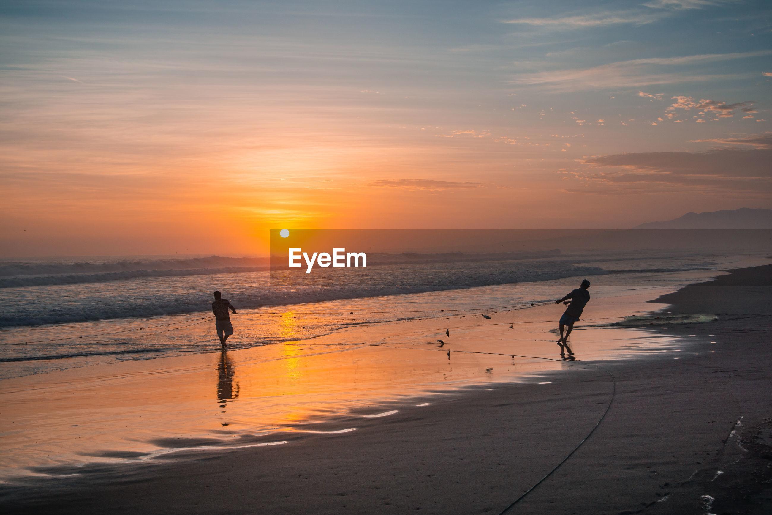 Silhouette fishermen fishing on shore at beach against orange sky