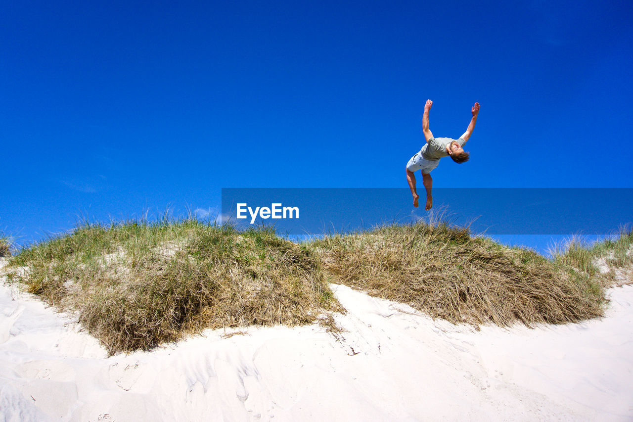 Low angle view of young man jumping at beach against blue sky