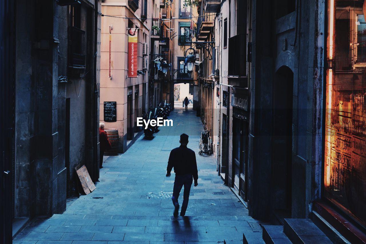 FULL LENGTH REAR VIEW OF A MAN WALKING ON NARROW STREET