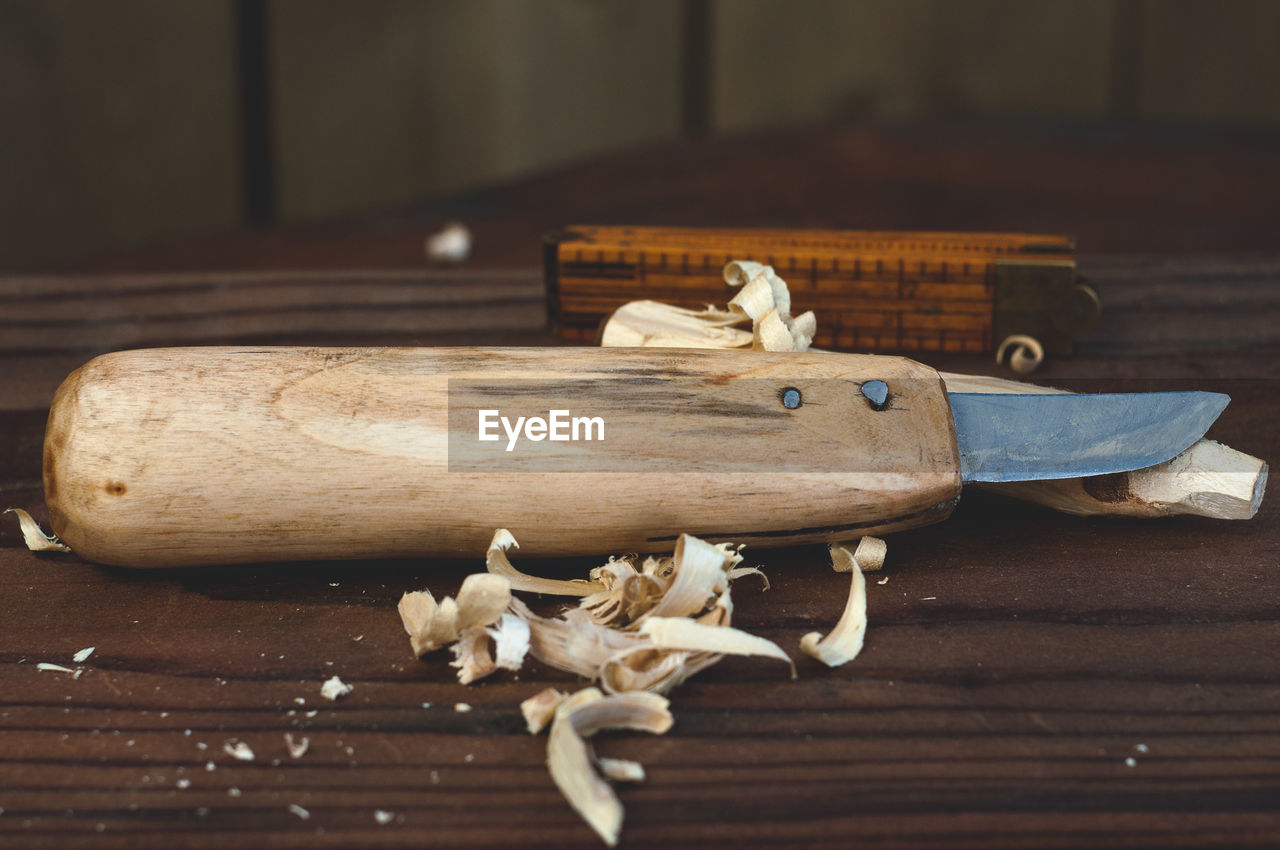 Close-Up Of Knife With Sawdust On Wooden Table