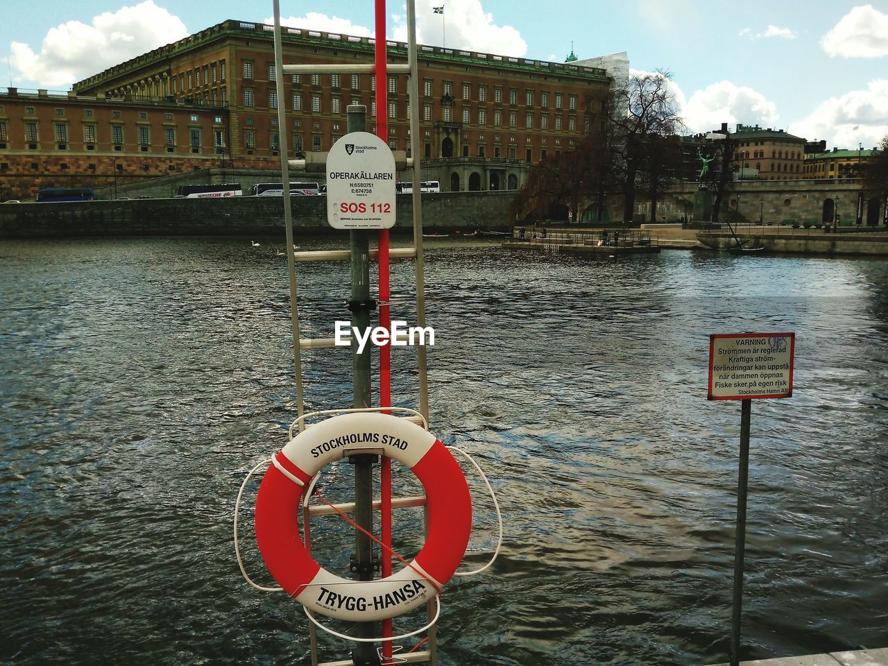 communication, text, water, safety, western script, life belt, warning sign, information sign, guidance, river, security, danger, hanging, day, symbol, protection, architecture, rescue, built structure, warning, building exterior, outdoors, road sign, sky, no people, red, nature, nautical vessel, close-up