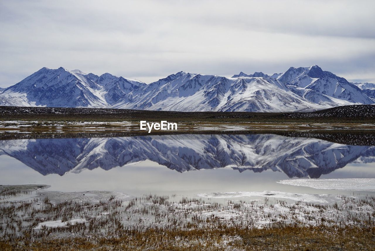 Scenic View Of Snowcapped Mountains Reflecting In Lake Against Cloudy Sky