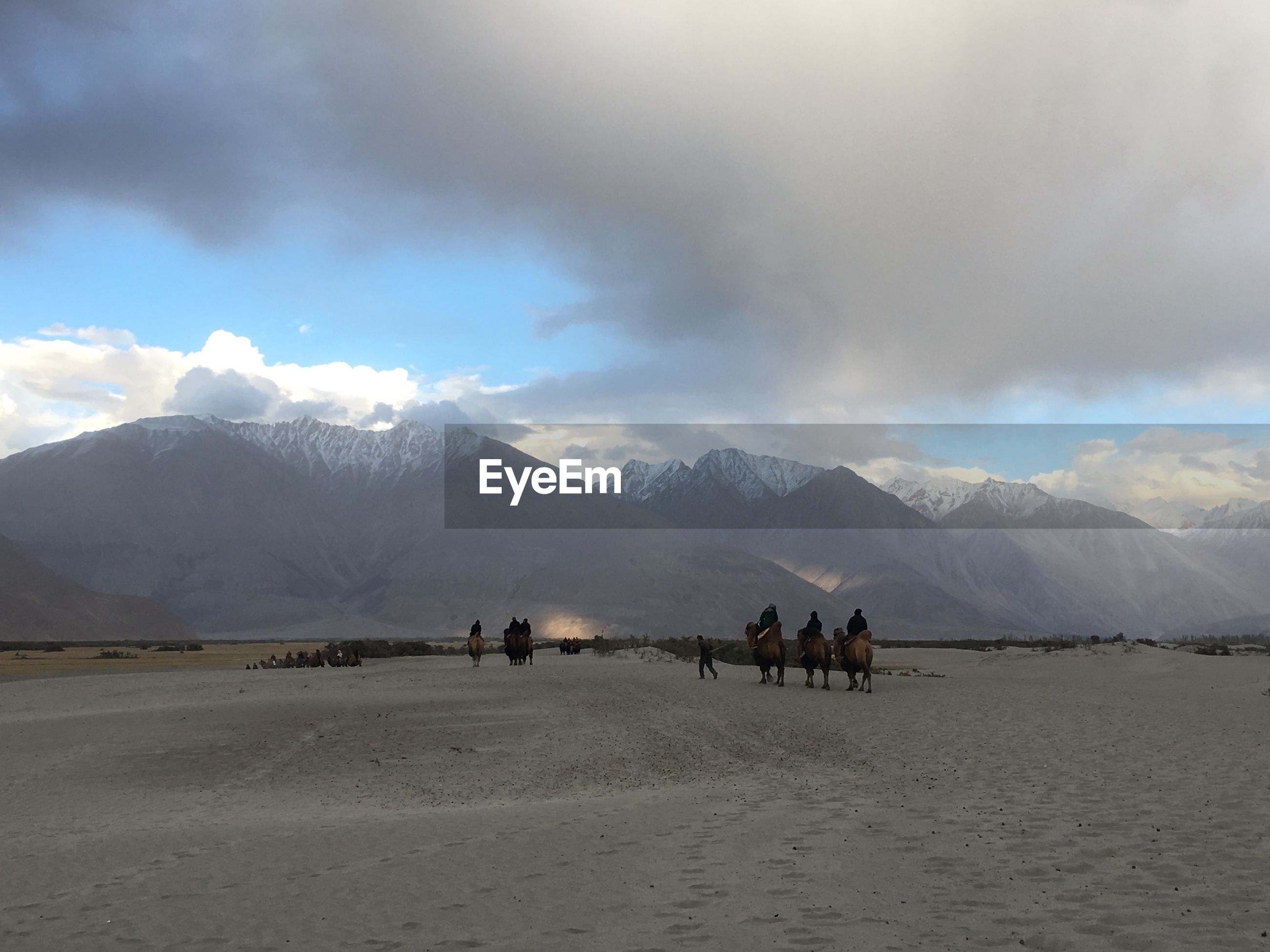 GROUP OF PEOPLE ON SNOWCAPPED MOUNTAINS AGAINST SKY