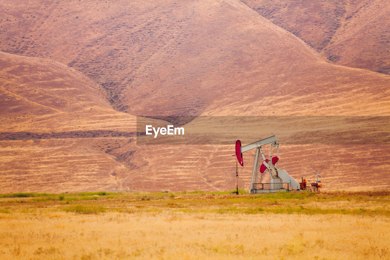 Drilling rig in desert against mountains