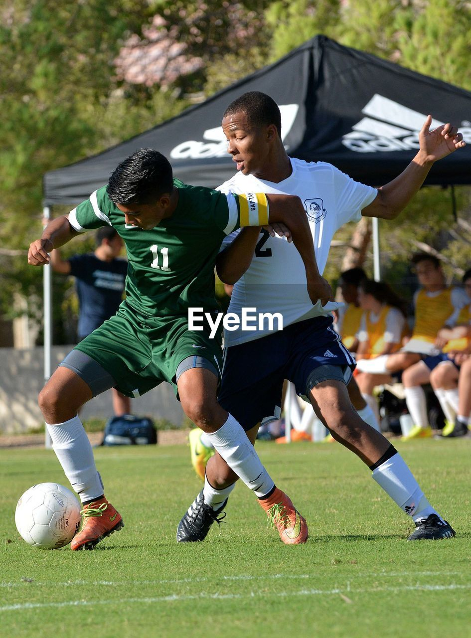 soccer, soccer ball, soccer player, sport, competition, kicking, motion, soccer uniform, effort, playing, competitive sport, running, activity, sports uniform, sports team, day, men, full length, sportsman, outdoors, grass, real people, soccer field, match - sport, young adult, athlete, offense - sporting position, only men, adult, people, adults only