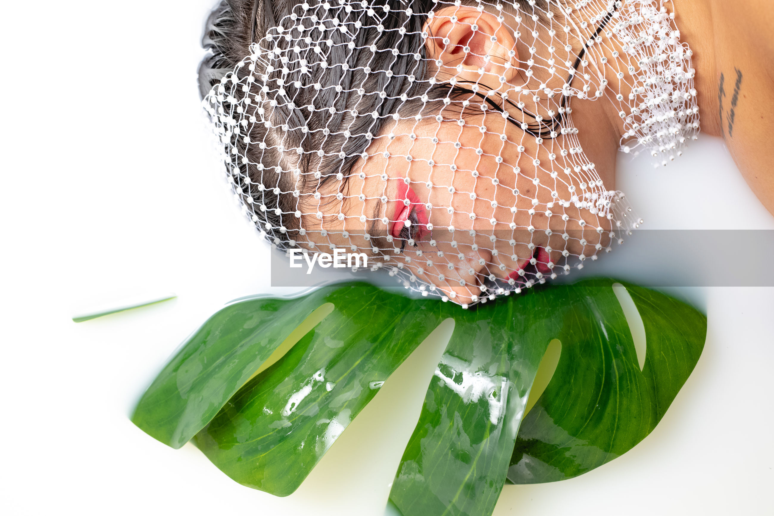 Close-up of thoughtful young woman with face covered by net taking milk bath