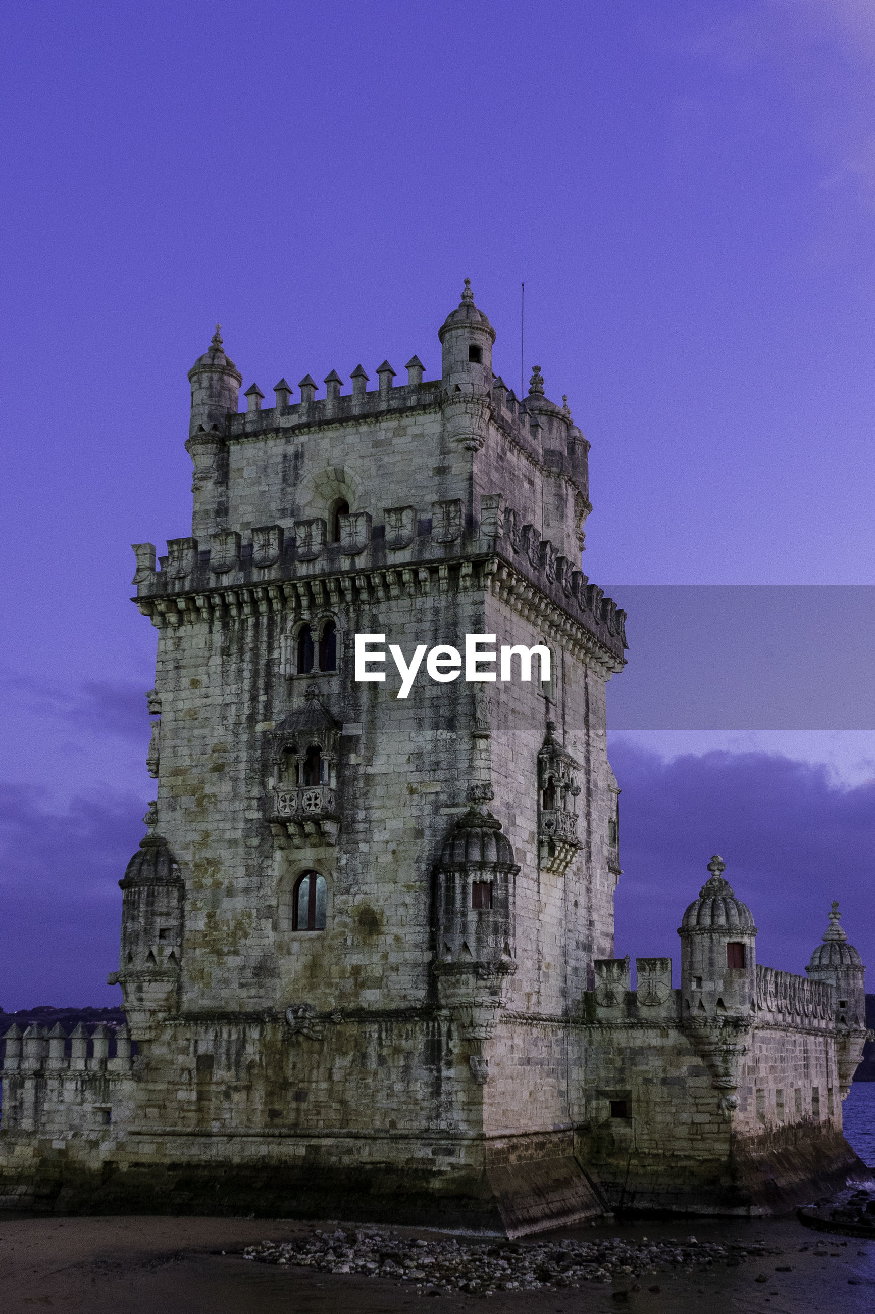 Low angle view of historic building called torre de belém in front of tejo river against sky