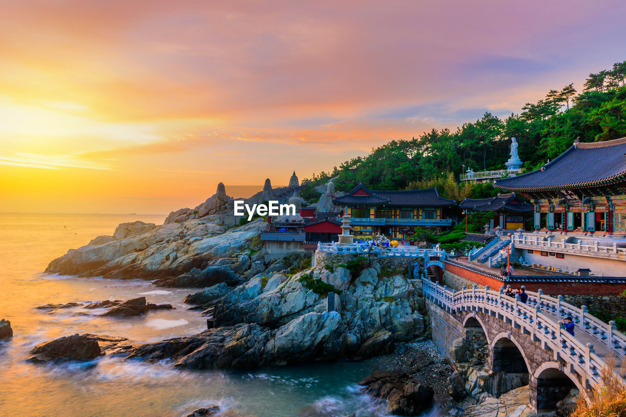 sunset, sky, water, architecture, built structure, cloud - sky, beauty in nature, scenics - nature, building exterior, nature, sea, orange color, rock, travel, rock - object, travel destinations, waterfront, no people, building