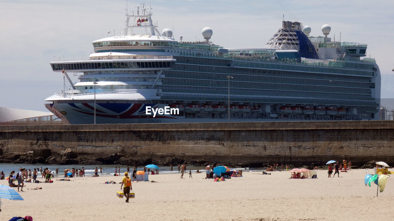 group of people, crowd, large group of people, real people, beach, water, land, leisure activity, vacations, architecture, men, holiday, sea, travel, trip, lifestyles, built structure, day, women, nature, outdoors, cruise ship, passenger craft
