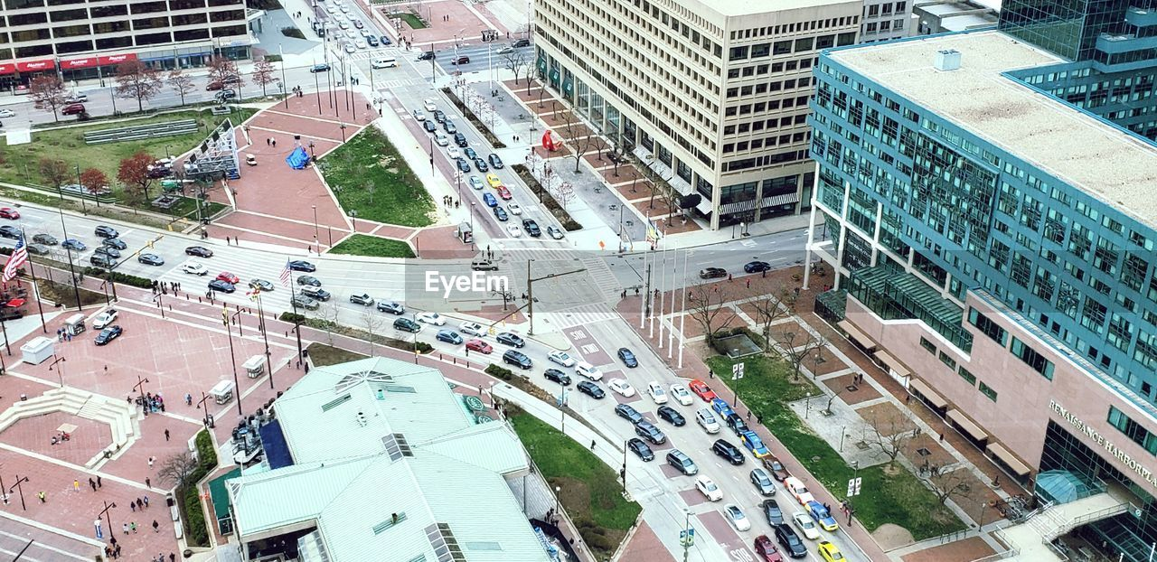 building exterior, city, built structure, architecture, high angle view, road, building, street, transportation, day, land vehicle, mode of transportation, incidental people, city street, city life, car, motor vehicle, residential district, outdoors, group of people, cityscape, office building exterior