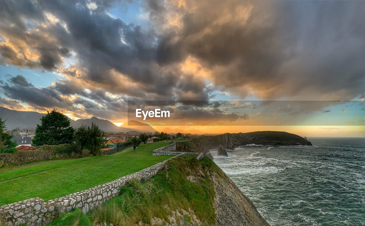 sky, cloud - sky, sunset, scenics - nature, beauty in nature, water, sea, nature, tranquil scene, architecture, tranquility, land, no people, built structure, orange color, idyllic, grass, overcast
