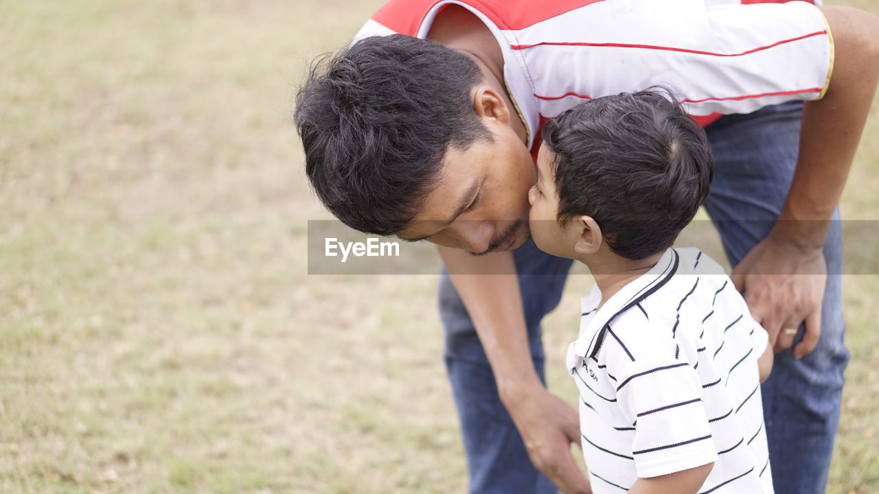 child, boys, men, childhood, males, two people, togetherness, family, real people, love, casual clothing, bonding, rear view, focus on foreground, day, people, emotion, leisure activity, lifestyles, positive emotion, son, outdoors, arm around, innocence