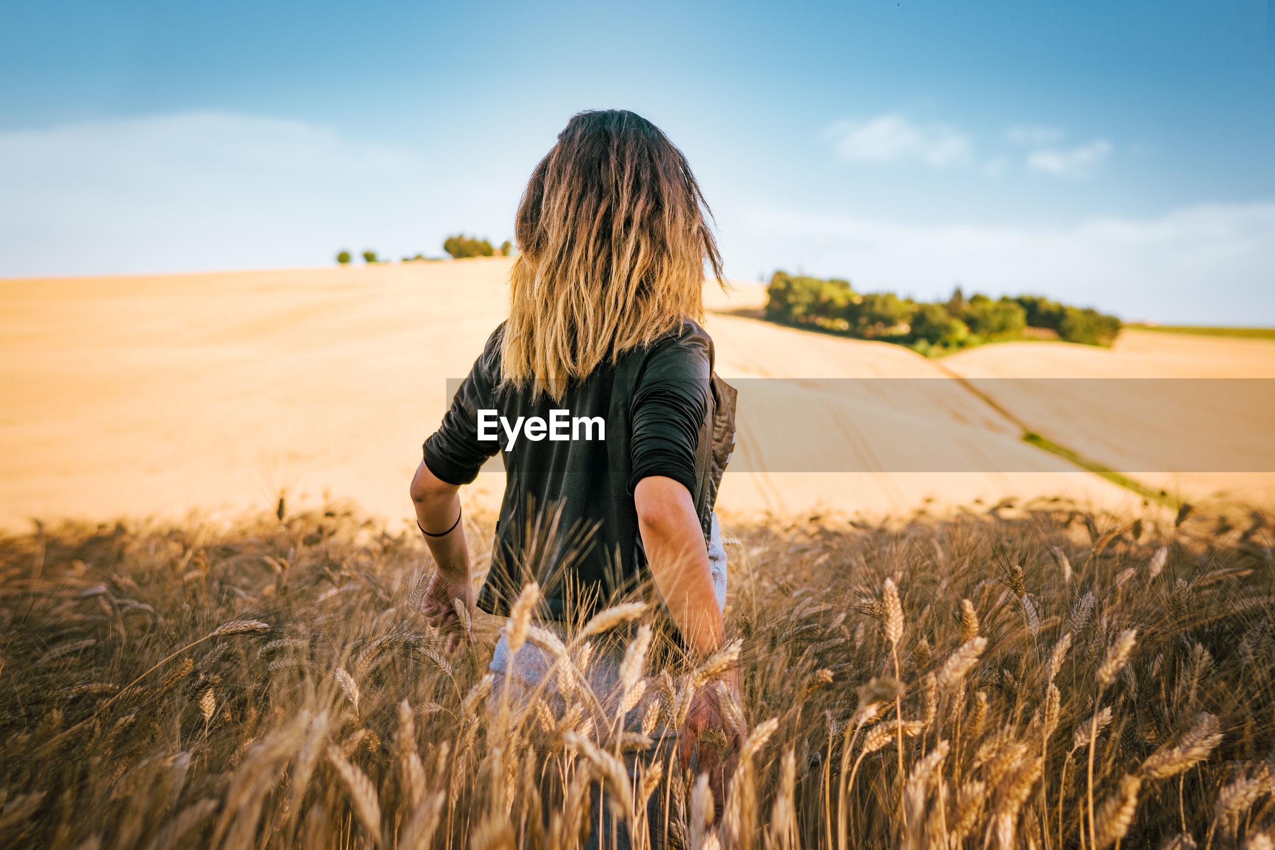 Rear view of woman in wheat field