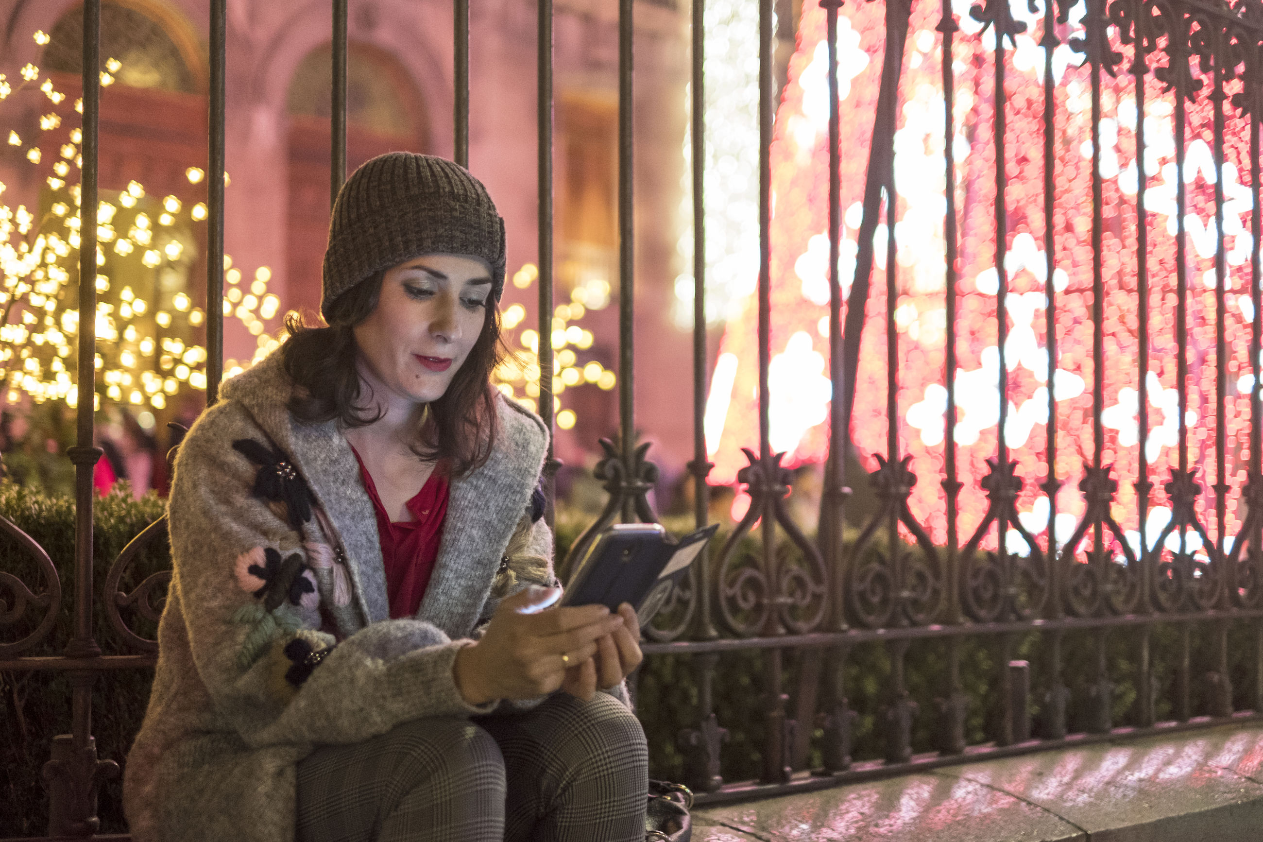 Woman using mobile phone while sitting in illuminated city at night