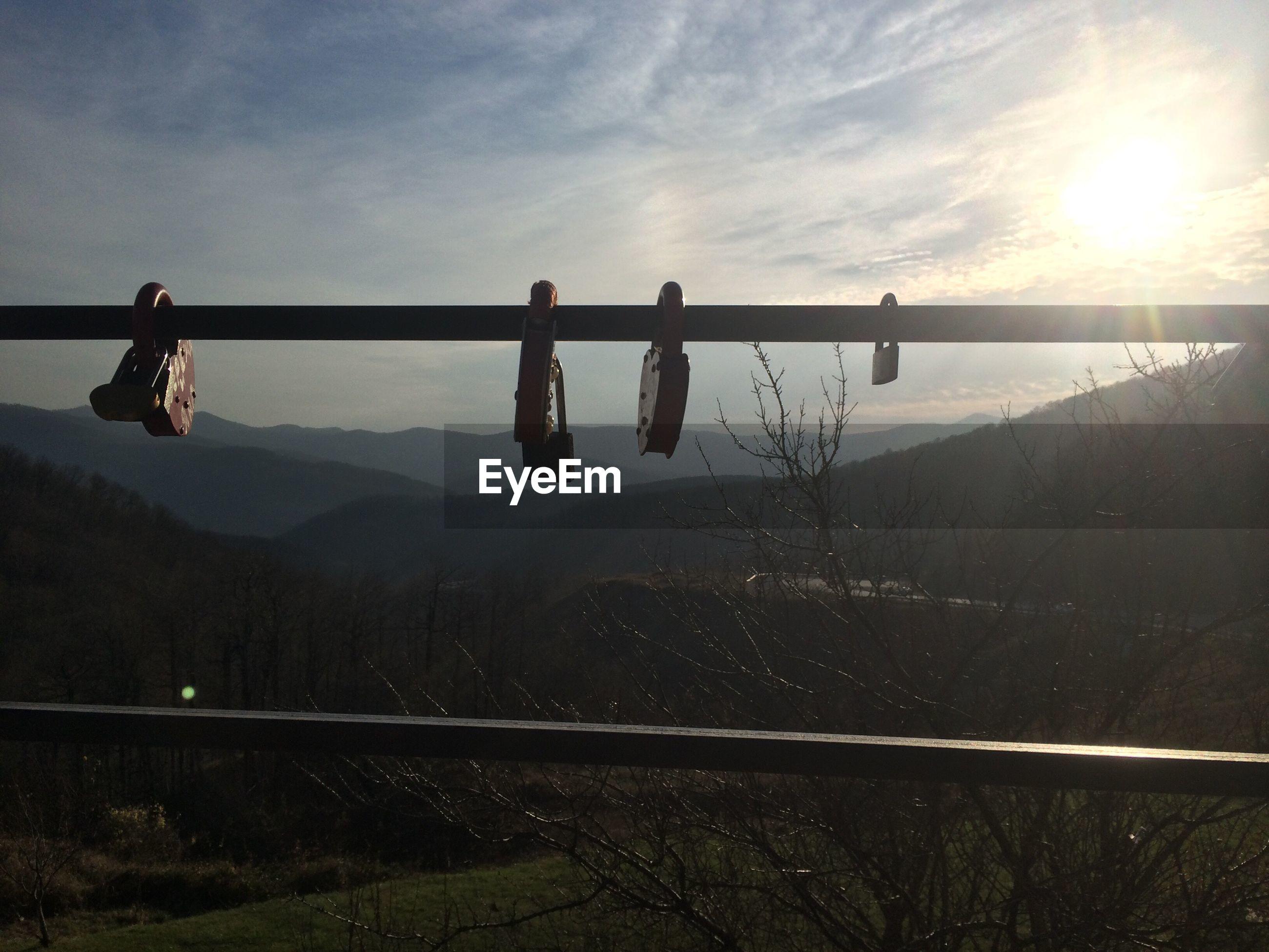 Padlocks hanging on railing against mountains