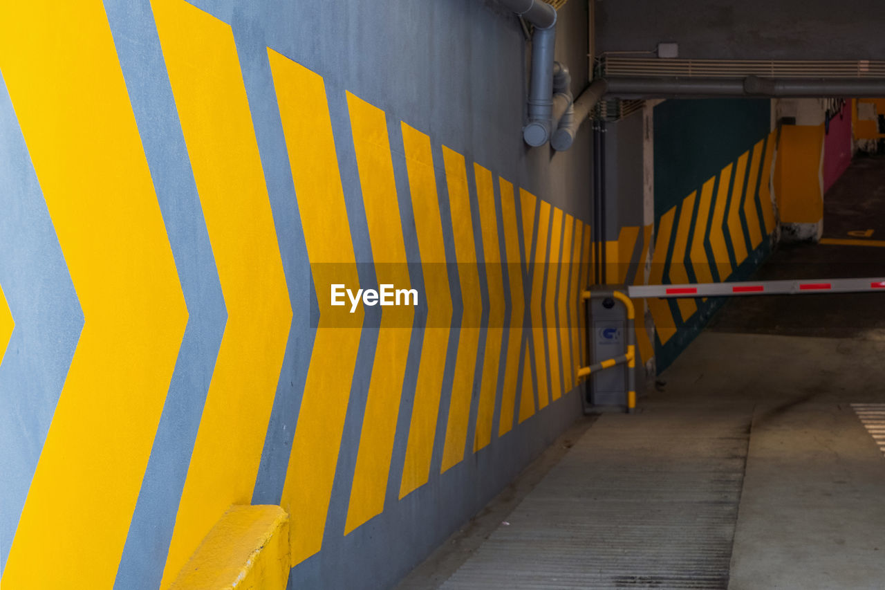 yellow, architecture, striped, built structure, wall - building feature, no people, pattern, building exterior, outdoors, multi colored, railing, day, security, building, staircase, empty, metal, direction, the way forward, protection