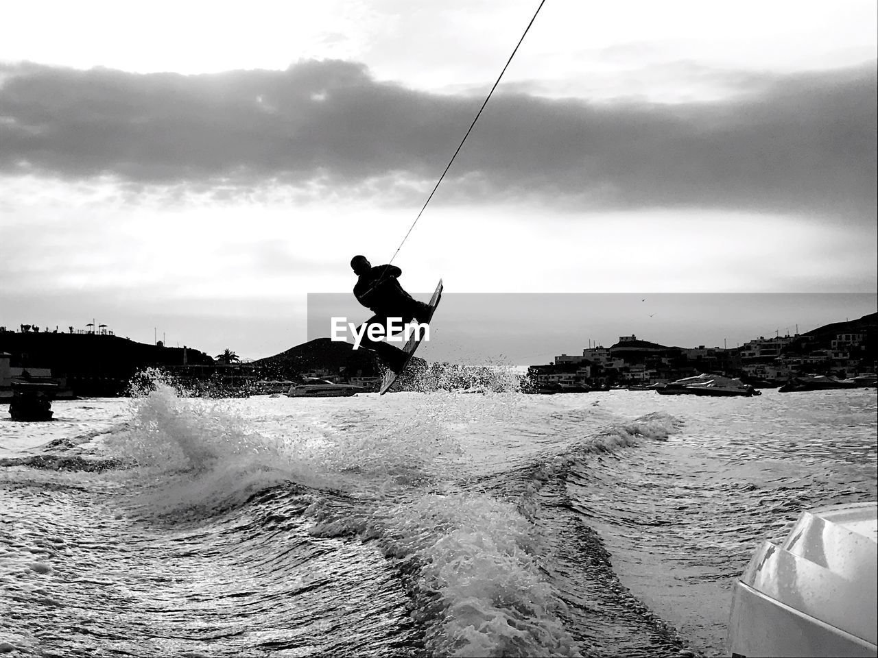 Rear View Of Man Kiteboarding On Sea Against Sky