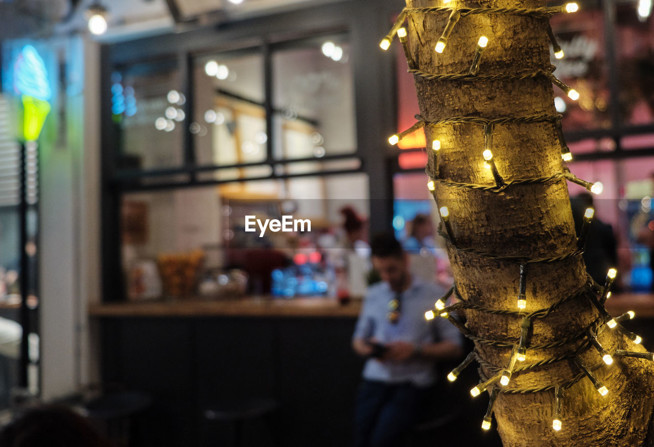 illuminated, focus on foreground, incidental people, lighting equipment, real people, celebration, decoration, indoors, restaurant, lifestyles, glass - material, religion, close-up, electric light, christmas, spirituality, one person, night, belief