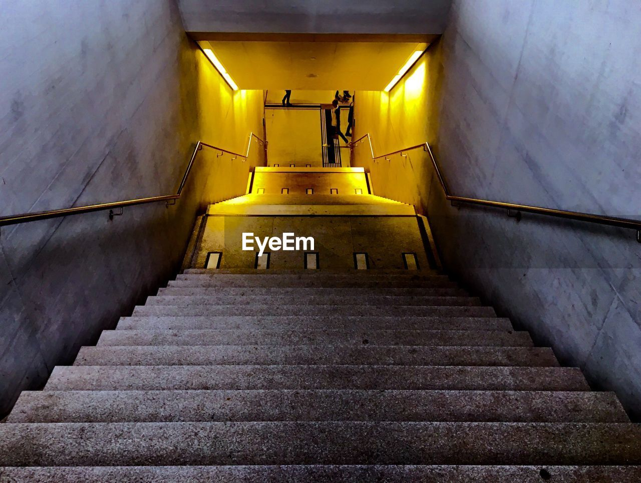 staircase, architecture, steps and staircases, built structure, the way forward, direction, railing, low angle view, no people, illuminated, indoors, wall - building feature, yellow, building, empty, lighting equipment, leadership, ceiling