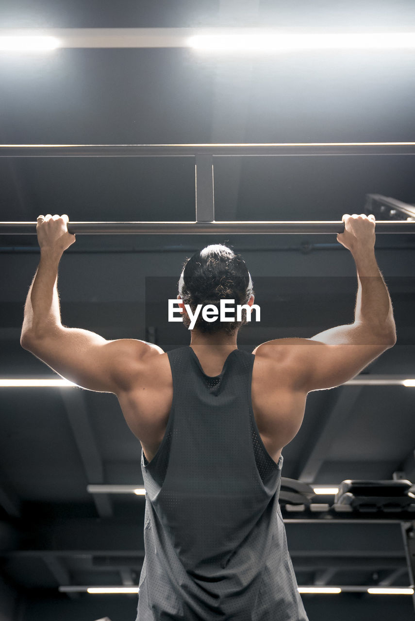 sport, exercising, one person, indoors, strength, lifestyles, healthy lifestyle, men, determination, muscular build, three quarter length, rear view, gym, real people, human arm, athlete, standing, arms raised, adult, effort, human limb, physical activity
