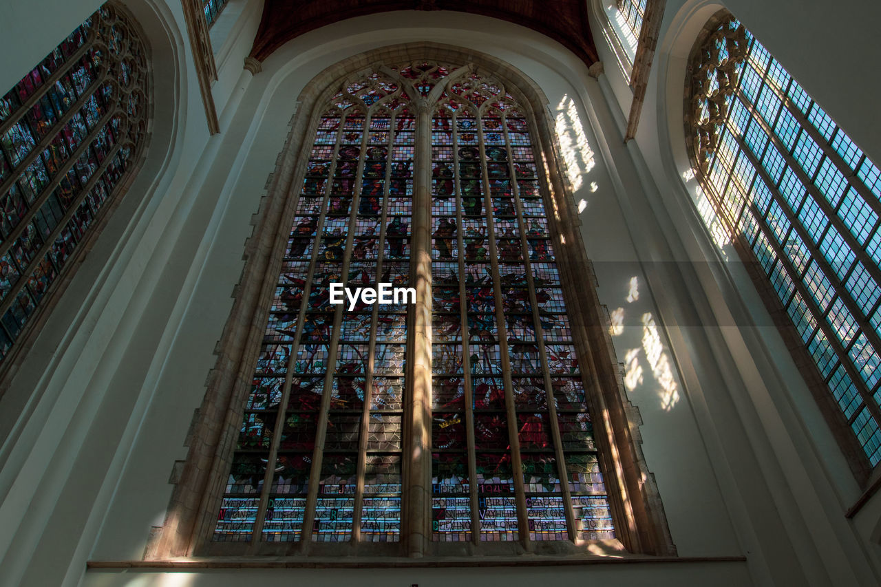 architecture, low angle view, built structure, indoors, religion, building, place of worship, belief, spirituality, stained glass, glass, glass - material, no people, ceiling, window, art and craft, architecture and art, ornate