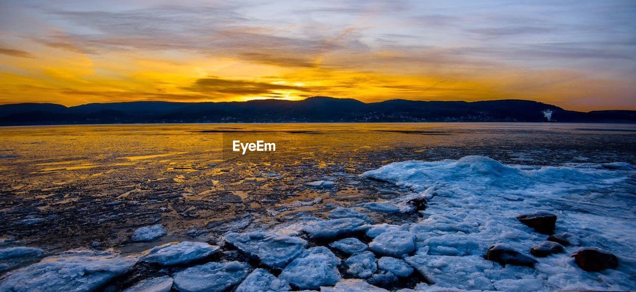 FROZEN LAKE AGAINST DRAMATIC SKY DURING SUNSET
