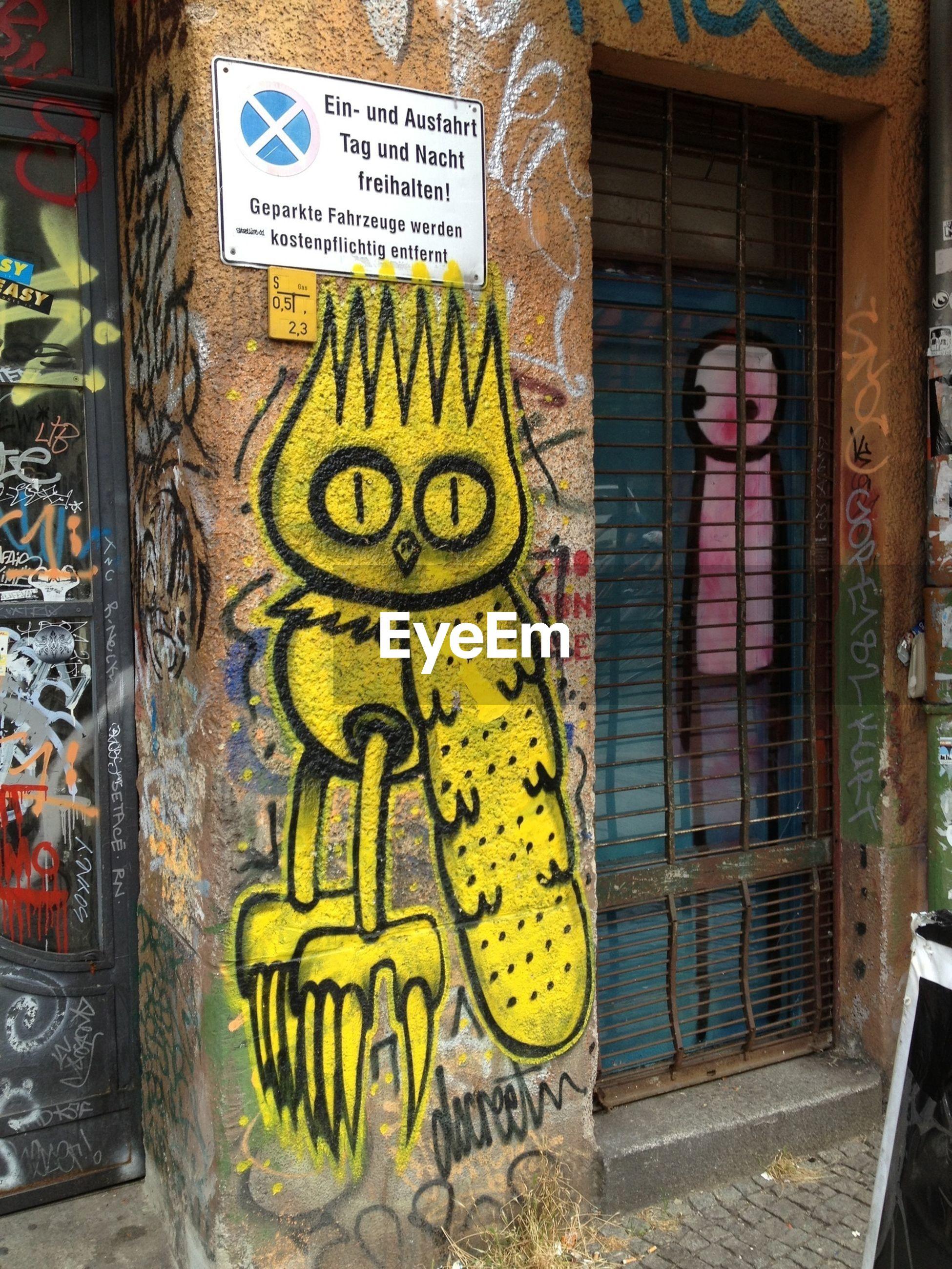 text, western script, communication, graffiti, non-western script, building exterior, architecture, wall - building feature, built structure, art, street art, art and craft, creativity, yellow, door, day, wall, outdoors, human representation, information sign
