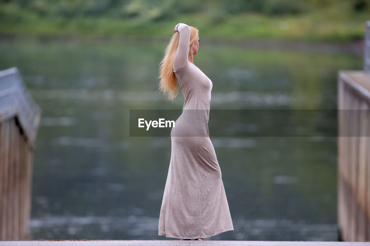 SIDE VIEW OF WOMAN STANDING ON LAKE
