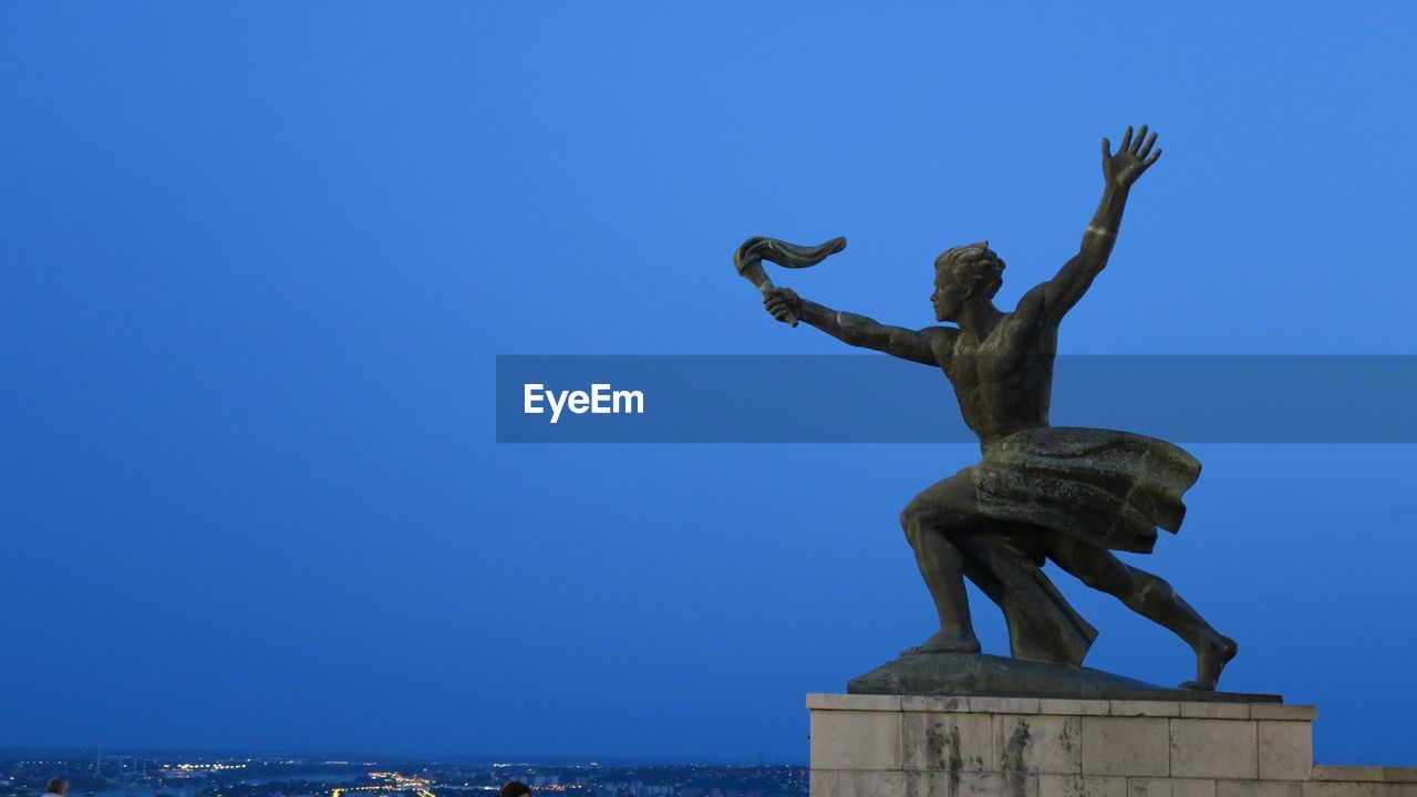 sculpture, sky, statue, art and craft, human representation, clear sky, blue, representation, copy space, no people, nature, male likeness, architecture, low angle view, creativity, history, day, the past, craft, travel destinations, arms raised