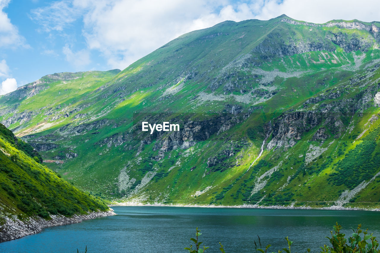 Scenic View Of Lake Amidst Mountains Against Sky