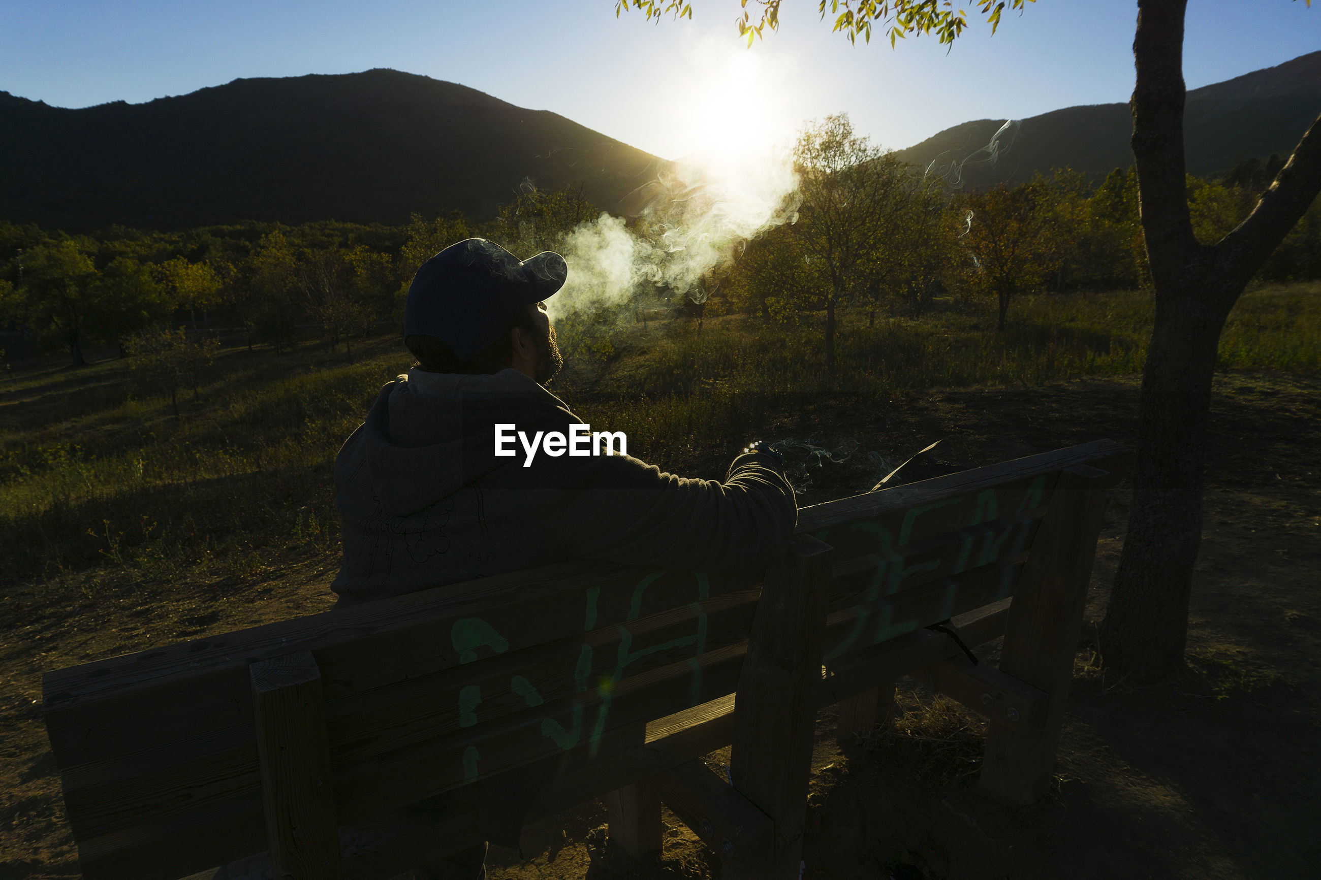Man smoking by field on bench during sunset