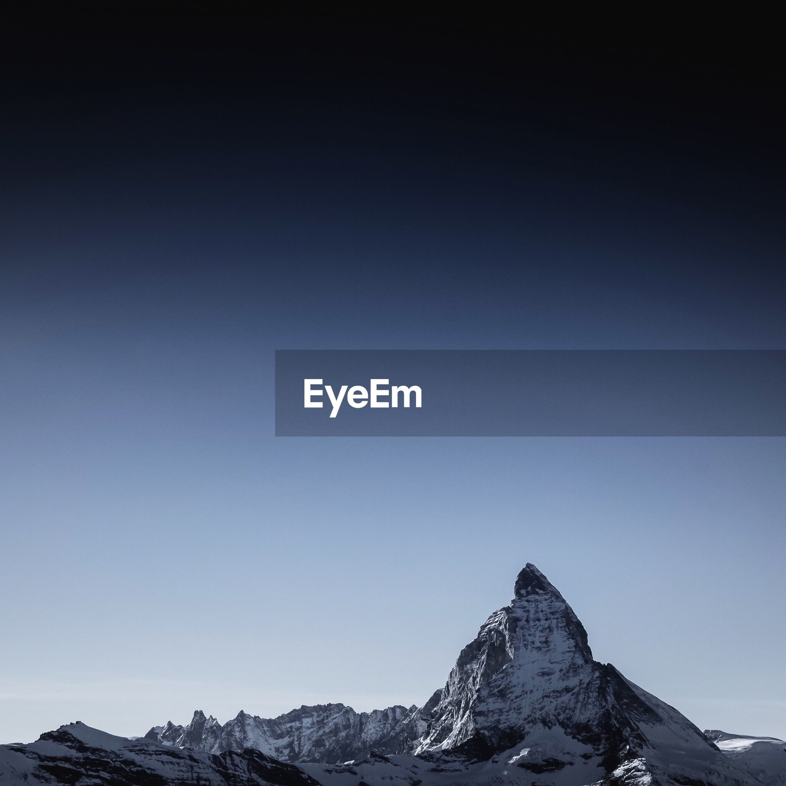 Snowcapped mountain against clear blue sky at dusk