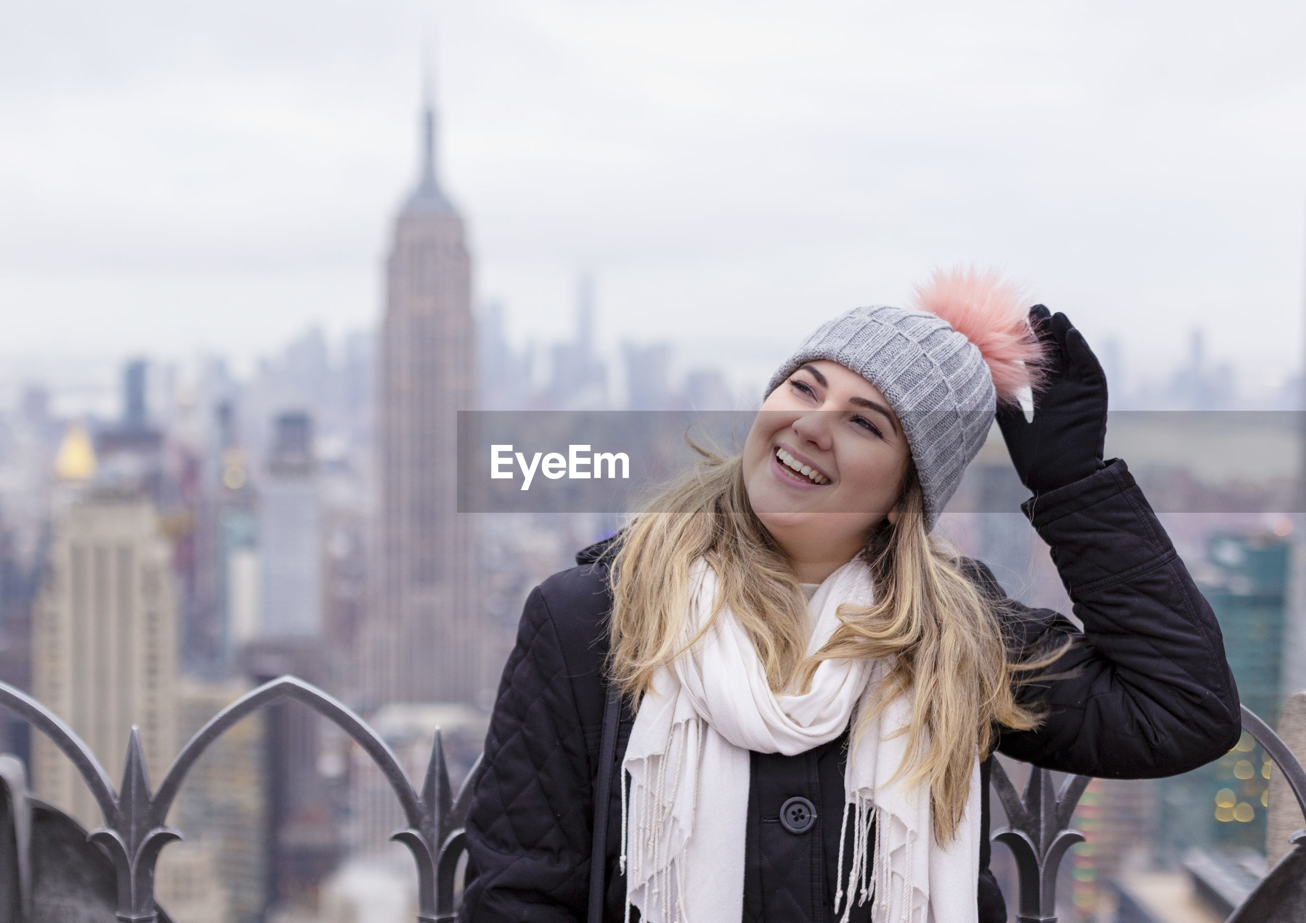 Portrait of smiling young woman against empire state building in city during winter